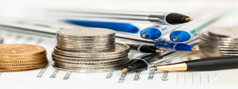 書類の上に積み上げられた硬貨とボールペン