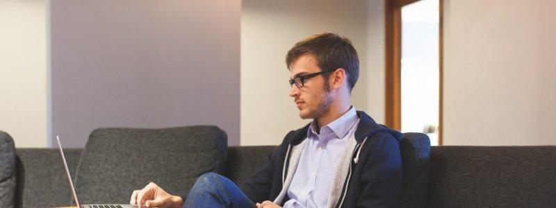 ソファーに座ってノートパソコンを見る男性
