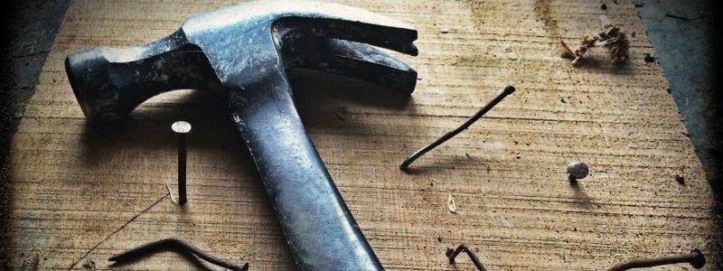 金づちと木材に刺さった釘