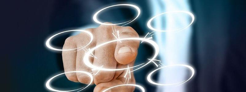 図の中央を指さす男性の手
