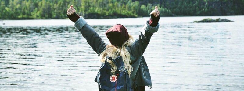 川沿いでバンザイする女性
