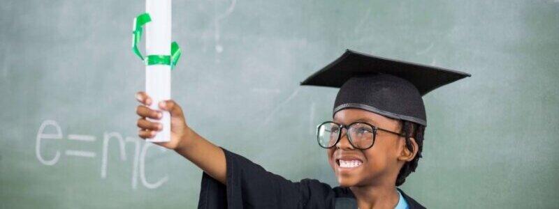 学位帽をかぶり、筒状の紙を掲げて笑う少年
