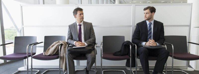 1つ空けて椅子に座るスーツの男性2人