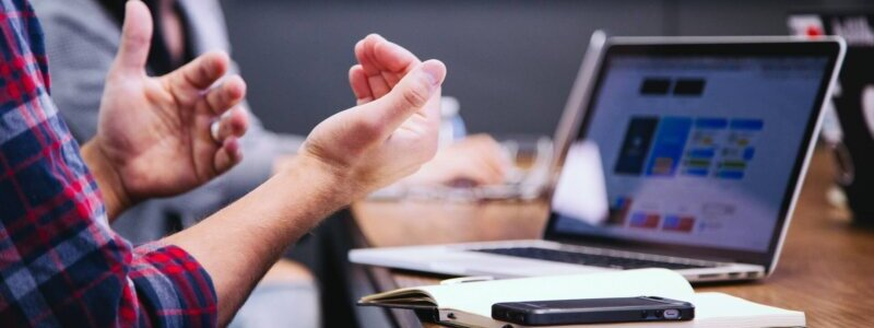 会議で手ぶりをする男性