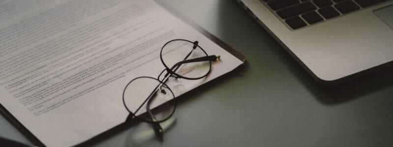 机の上に置かれた書類とメガネとノートパソコン