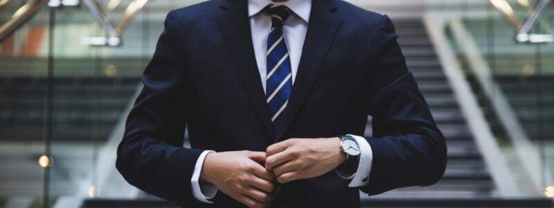 スーツの前ボタンを閉める男性