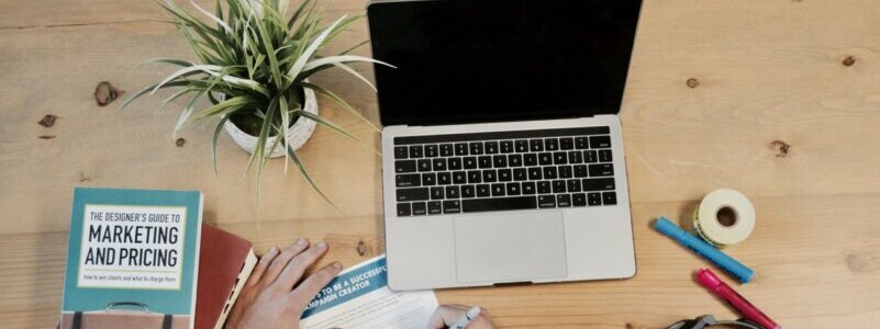 机の上のノートパソコン・本・観葉植物・ペン・メモを取る手