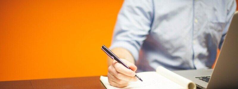 パソコンを見ながらノートにメモを取る男性